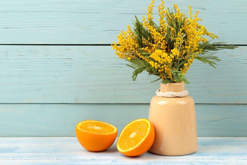 Красивые цветки желтой мимозы в керамических вазе и апельсине на голубой деревянной предпосылке Свободное место стоковые фотографии rf