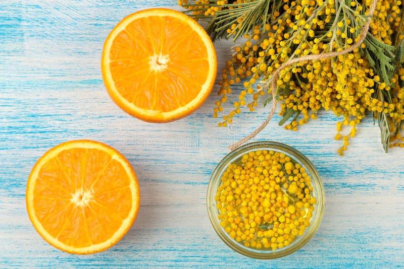 Красивые цветки желтых мимозы и апельсина на голубой деревянной предпосылке Взгляд сверху Конец-вверх стоковое изображение rf