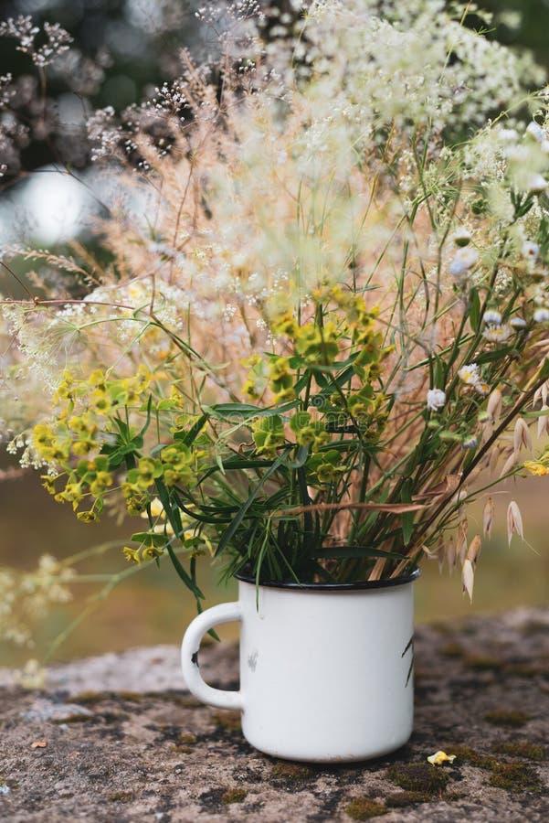 Красивые цветки поля, сельский букет в чашке белого металла стоковое изображение