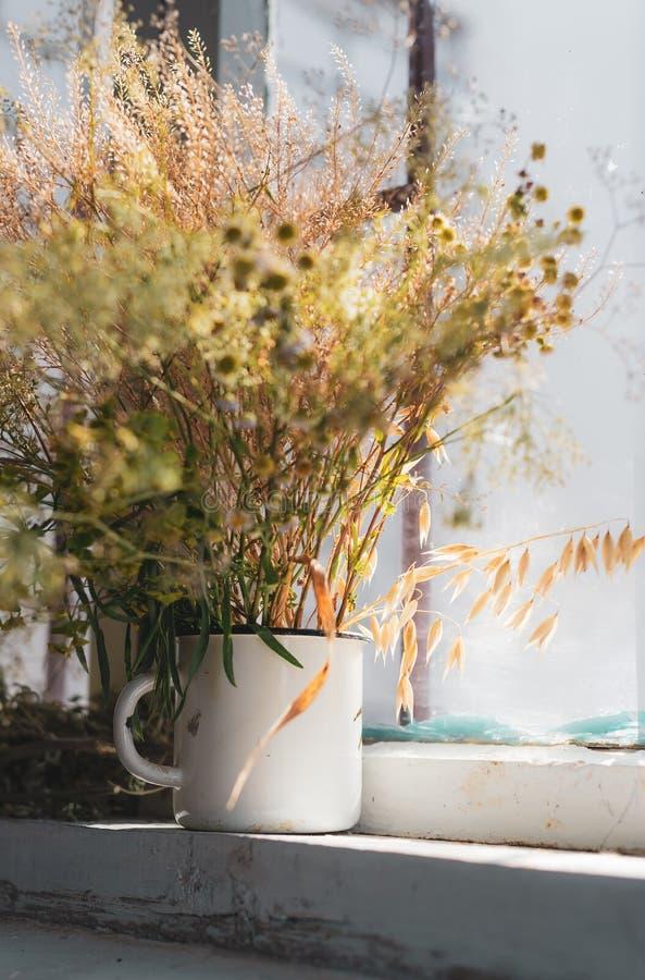 Красивые цветки поля, сельский букет в чашке белого металла стоковые изображения