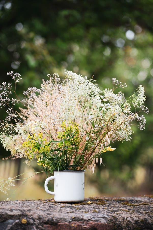 Красивые цветки поля, сельский букет в чашке белого металла стоковое фото rf