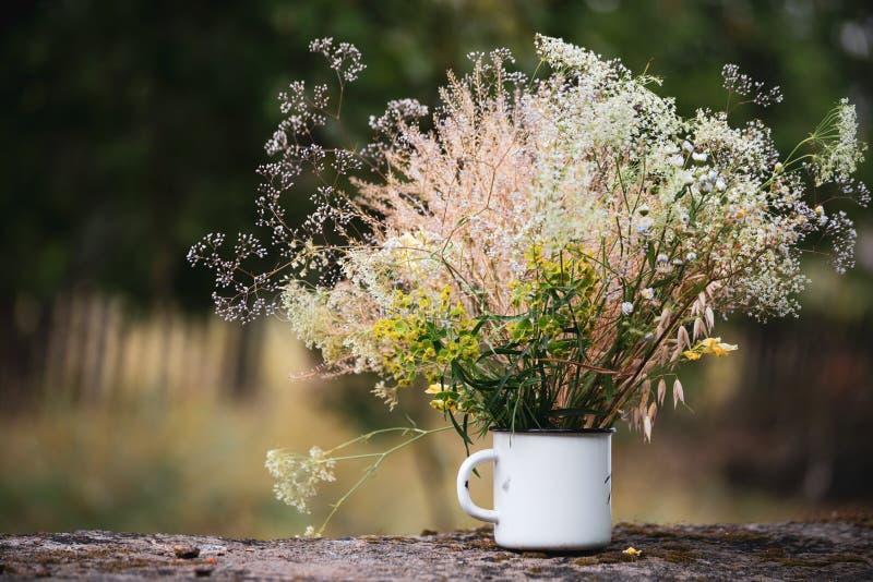 Красивые цветки поля, сельский букет в чашке белого металла стоковая фотография rf