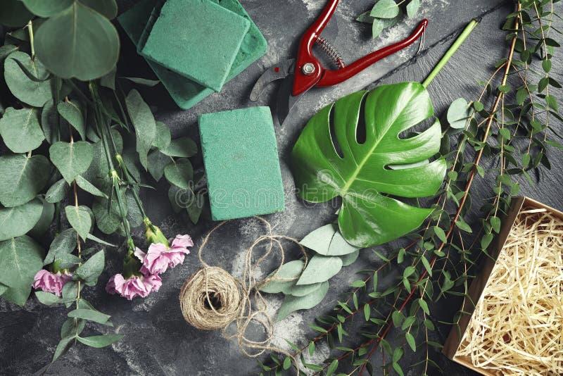 Красивые цветки с зелеными ветвями и поставками флориста на серой таблице стоковые фотографии rf