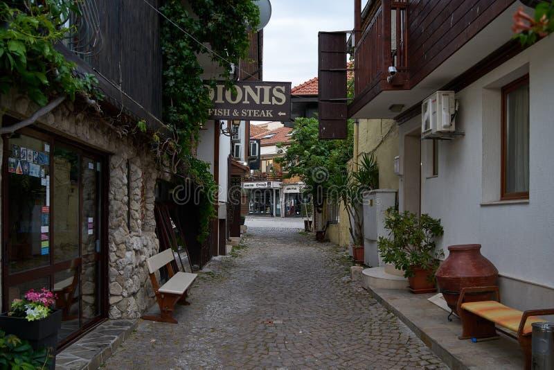 Красивые цветок и узкая улочка с ресторанами и кафами старого приморского города стоковые изображения