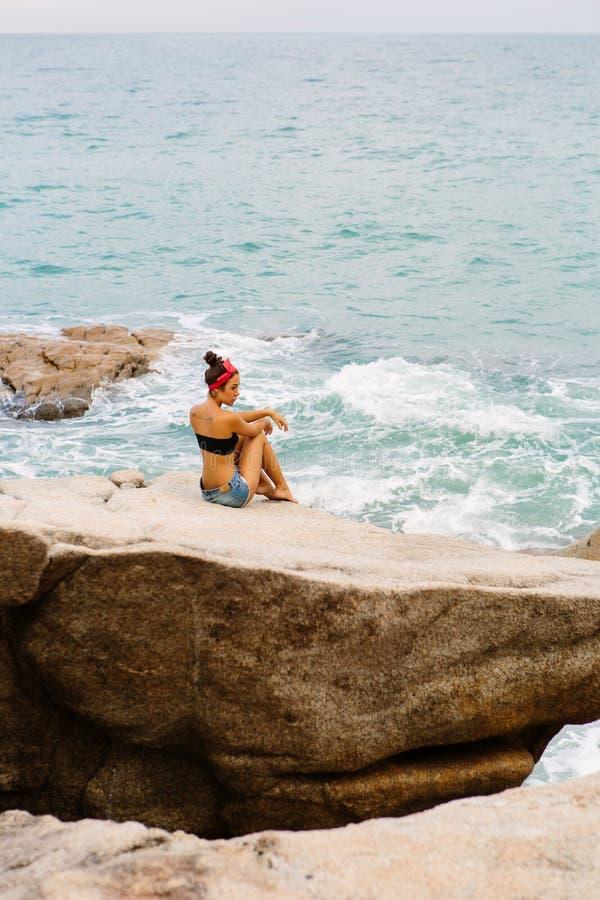 Красивые шорты девушки вкратце сидят на больших камнях стоковое изображение