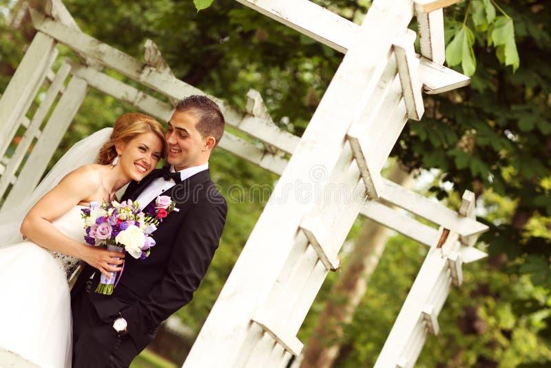 Красивые bridal пары имея потеху в парке на их букете цветка дня свадьбы стоковая фотография rf