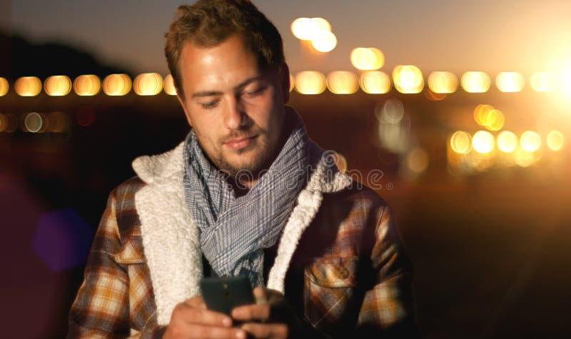 Красивые sms молодого человека отправляя СМС используя app на умном телефоне на autum стоковое фото