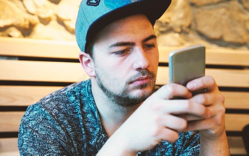 Красивые sms молодого человека отправляя СМС используя app на smartphone стоковые фотографии rf