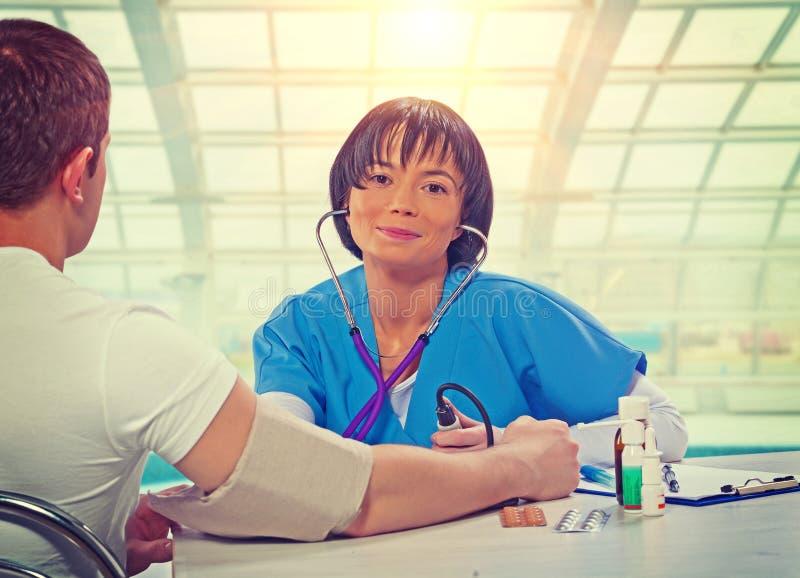 Красивый азиатский женский доктор сидя на таблице с пациентом стоковые фотографии rf