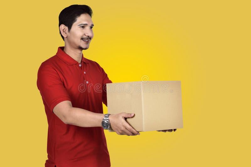 Красивый азиатский работник доставляющий покупки на дом давая пакет стоковое фото