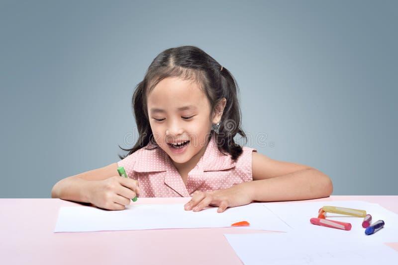 Красивый азиатский чертеж маленькой девочки с crayons воска стоковые фотографии rf