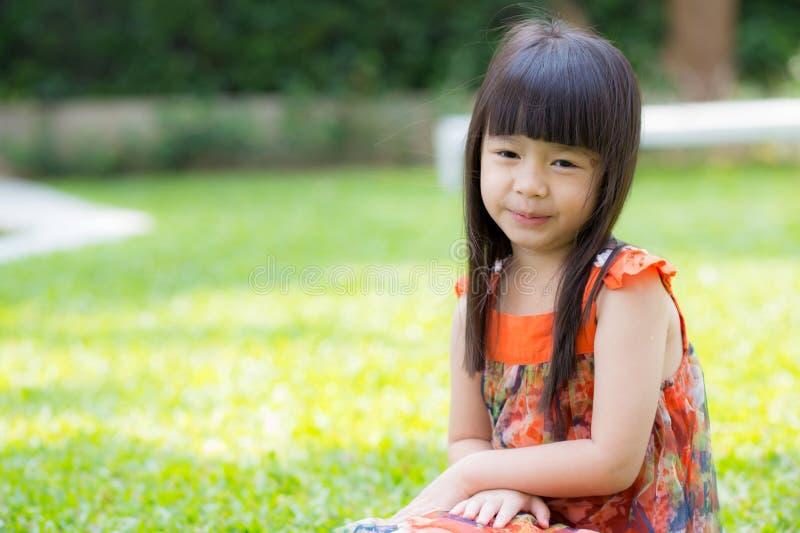 Красивый азиат маленькой девочки портрета усмехаясь сидеть на зеленой траве на парке стоковое изображение rf