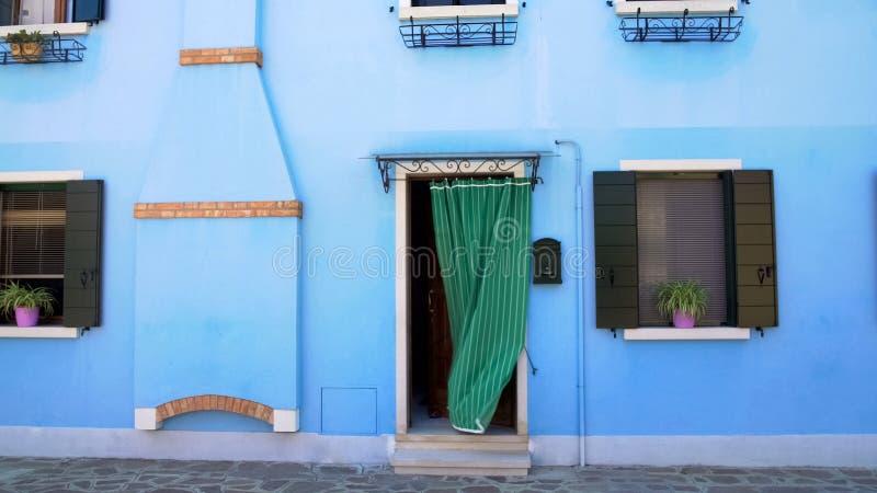 Красивый аккуратный голубой дом с цветочными горшками на окнах, остров Burano, Венеция стоковое фото rf