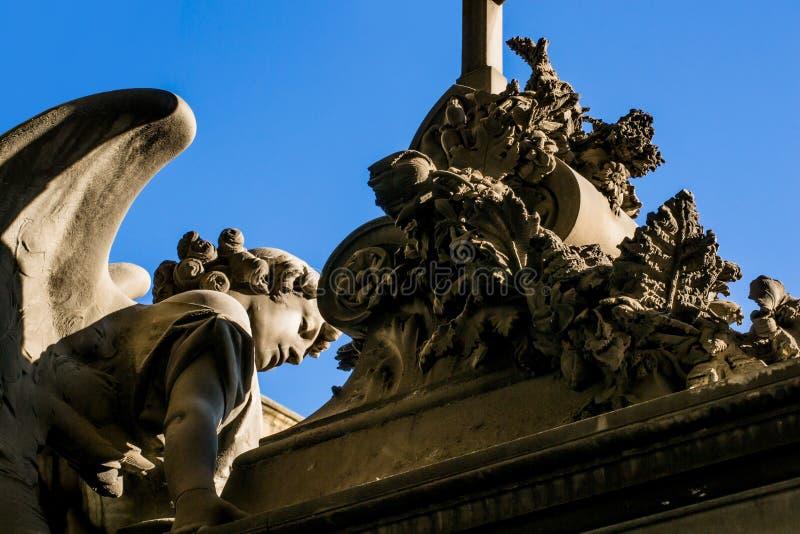 Красивый ангел при крыла сделанные камня сидя рядом с украшениями стоковое фото
