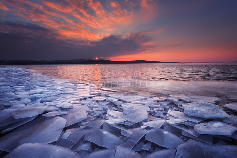 Красивый ландшафт зимы с небом захода солнца пламенистым и замороженным озером Состав природы стоковое изображение