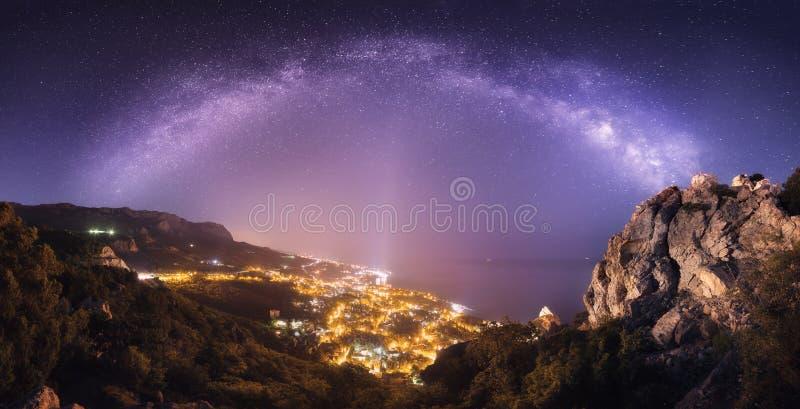 Красивый ландшафт ночи с млечным путем против города освещает стоковая фотография rf