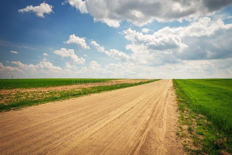 Красивый ландшафт с дорогой, зелеными полями и облачным небом стоковое фото rf