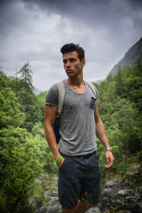 Красивый атлетический молодой человек с рюкзаком в держателе стоковое фото rf