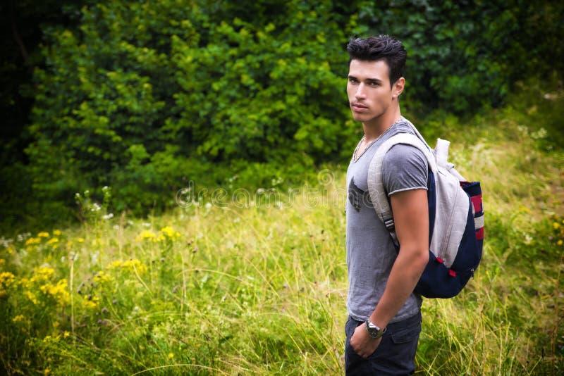 Красивый атлетический молодой человек с рюкзаком в держателе стоковое изображение