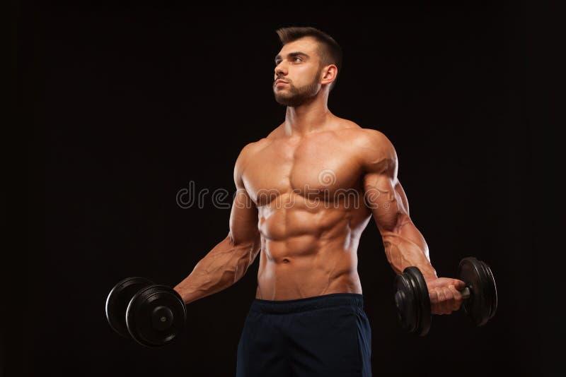 Красивый атлетический человек в спортзале нагнетает вверх muscles с гантелями в спортзале Тело фитнеса мышечное изолированное на  стоковое фото rf