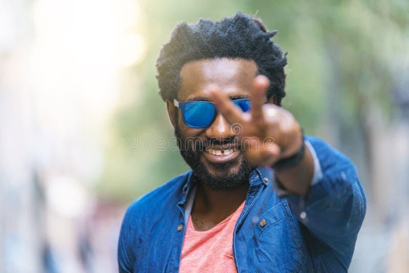 Красивый африканский молодой человек делая знак победы стоковое изображение rf