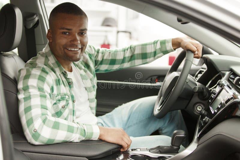 Красивый африканский человек выбирая новый автомобиль на дилерских полномочиях стоковая фотография