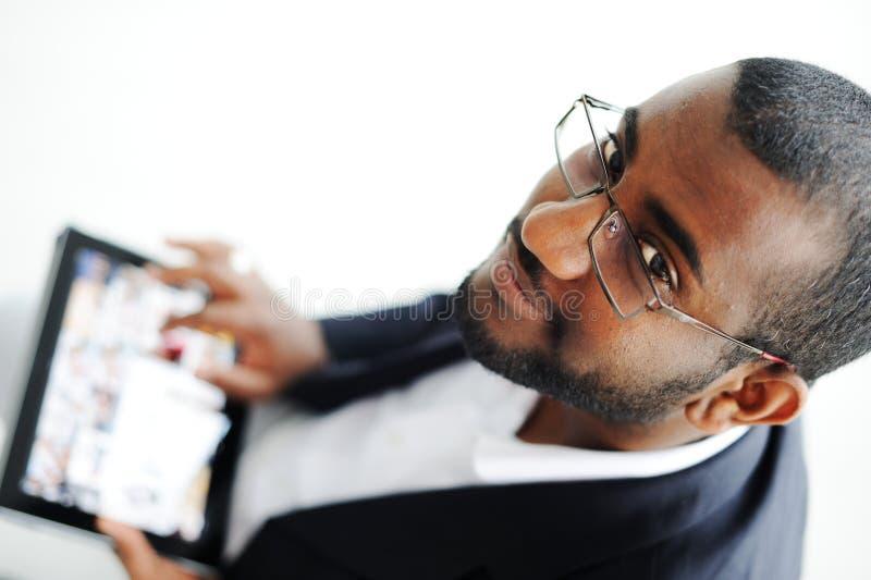 Красивый африканский человек с компьютером таблетки