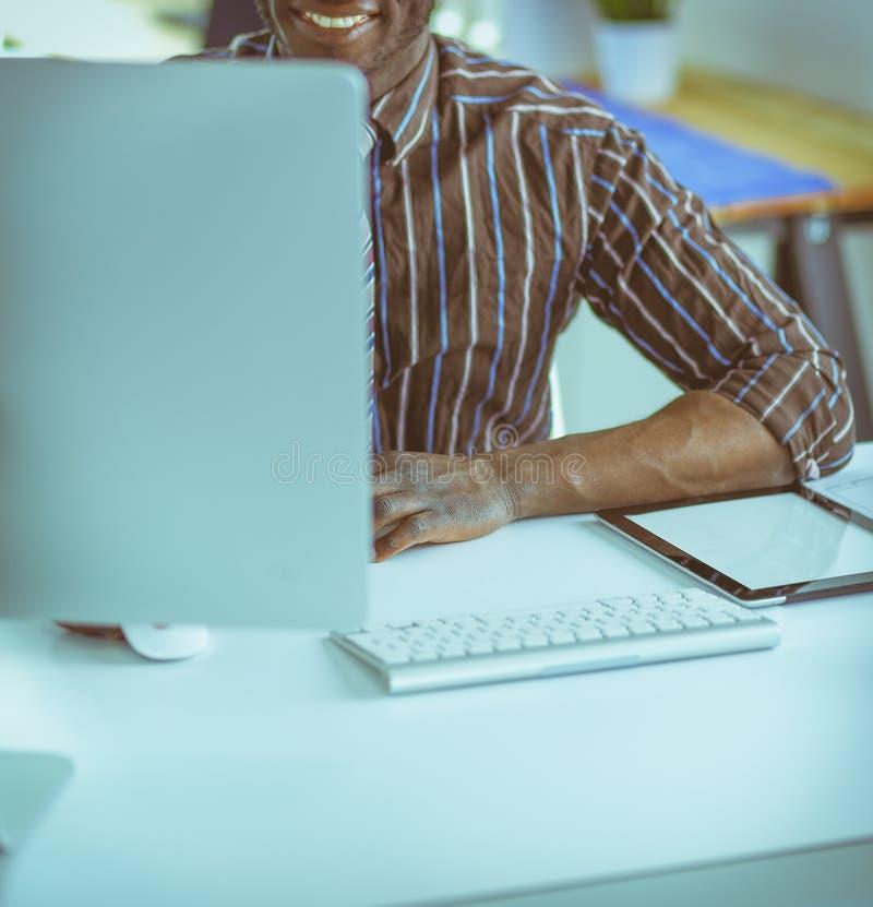 Красивый афро американский бизнесмен в классическом костюме использует ноутбук и усмехается пока работающ в офисе стоковые изображения rf