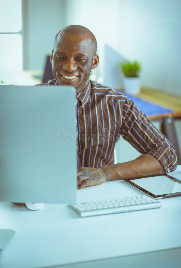 Красивый афро американский бизнесмен в классическом костюме использует ноутбук и усмехается пока работающ в офисе стоковое фото