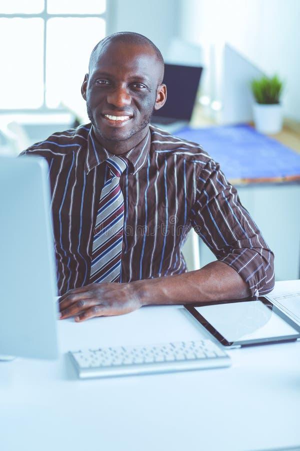 Красивый афро американский бизнесмен в классическом костюме использует ноутбук и усмехается пока работающ в офисе стоковые фото