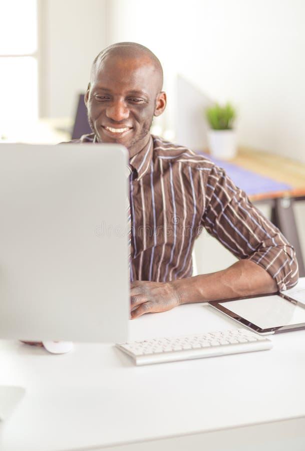 Красивый афро американский бизнесмен в классическом костюме использует ноутбук и усмехается пока работающ в офисе стоковое фото rf