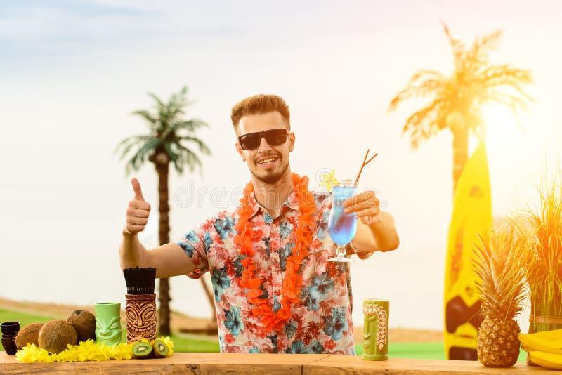 Красивый бармен стоя около счетчика бара, подготавливая кран стоковое изображение