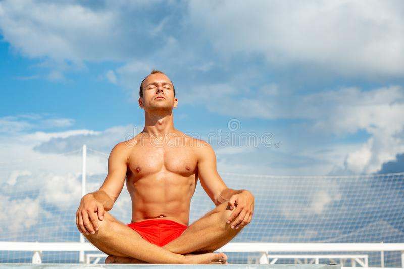 Красивый без рубашки молодой человек во время раздумья или делать внешнюю тренировку йоги сидя против голубого неба стоковое фото