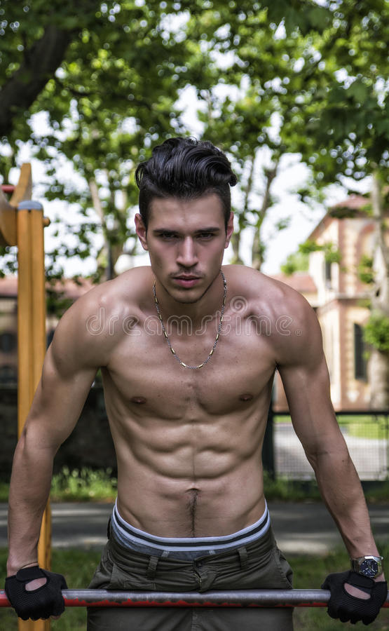 Красивый без рубашки молодой человек работая в внешнем спортзале в парке стоковое фото rf