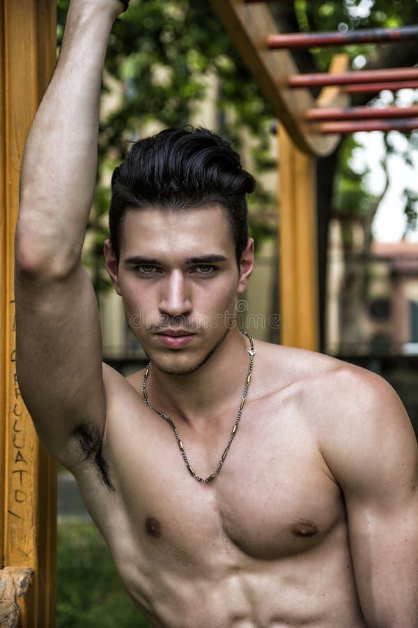 Красивый без рубашки молодой человек работая в внешнем спортзале в парке стоковая фотография rf
