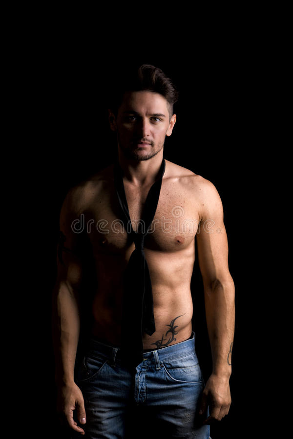 Красивый без рубашки мышечный человек стоя на темноте стоковое изображение rf