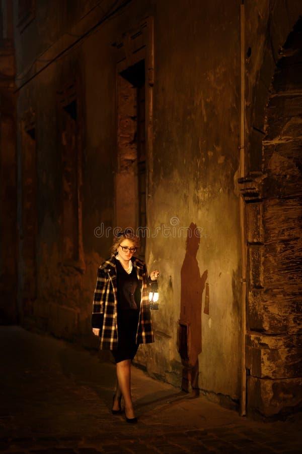 Красивый белокурый женский сыщик с винтажным фонариком в ретро стоковая фотография rf