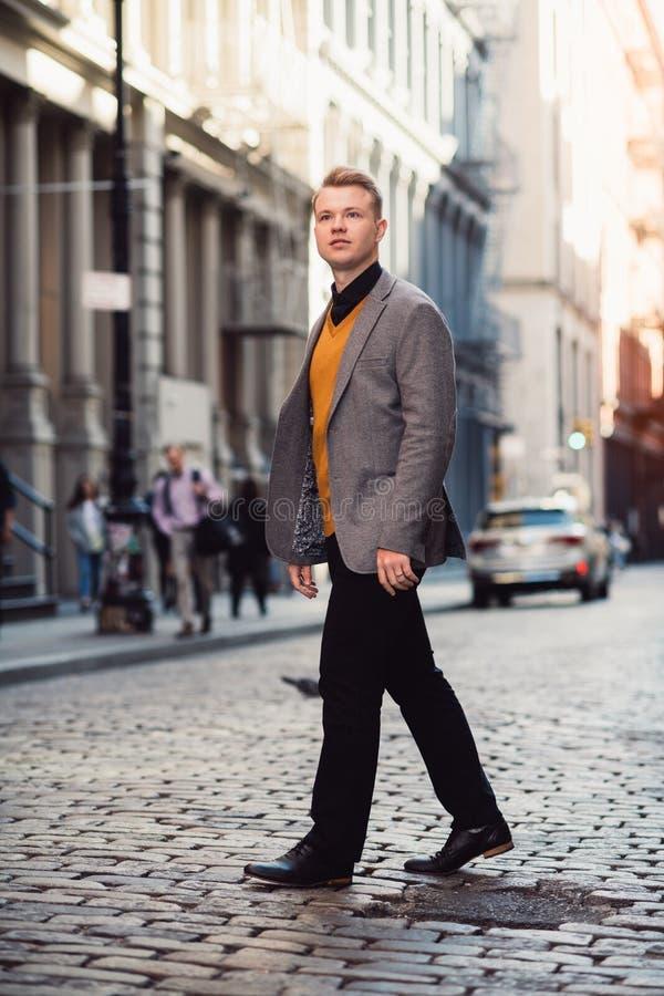 Красивый белокурый человек идя на улицу города нося умное случайное обмундирование с курткой и черными брюками в distr Нью-Йорка  стоковые изображения