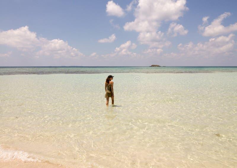 Красивый берег в острове Karimunjawa с девушкой которое идет в воду стоковые фотографии rf