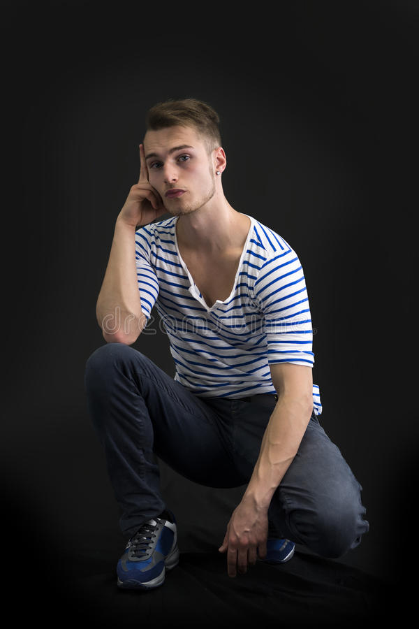 Красивый белокурый молодой человек сидя на черной предпосылке стоковые изображения rf