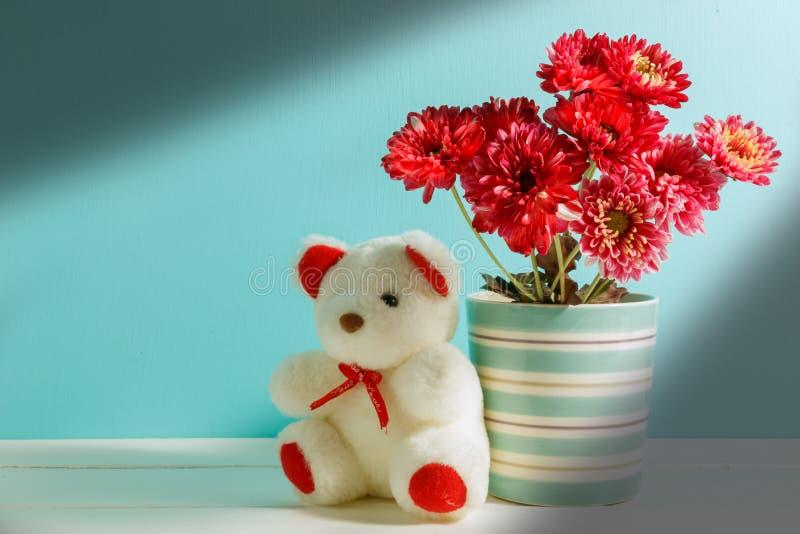 красивый белый плюшевый медвежонок, розовый цветок в вазе на белом, зеленом wo стоковое изображение rf