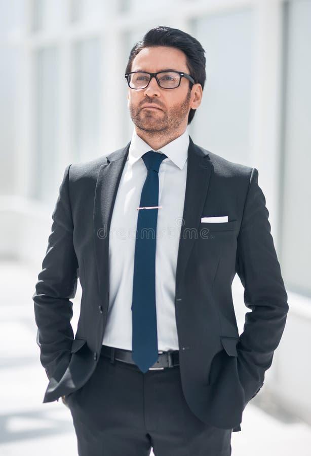 Красивый бизнесмен в предпосылке офиса стоковые изображения rf