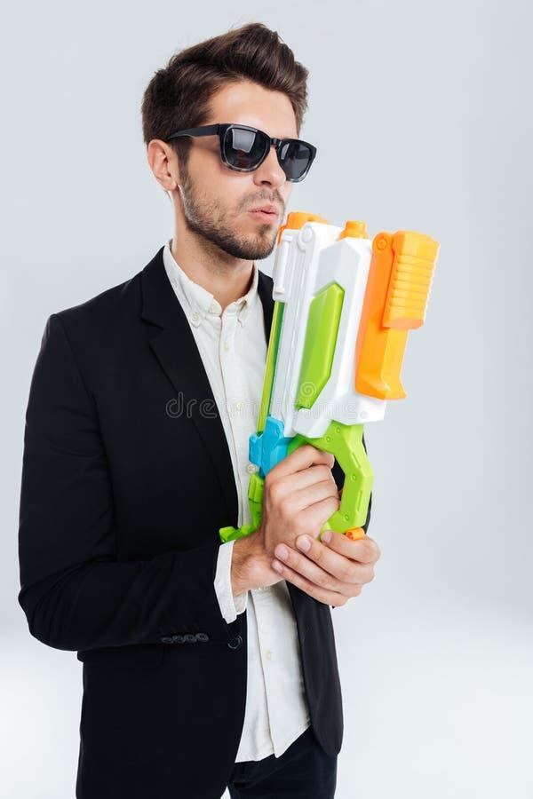 Красивый бизнесмен в черных suglasses держа красочный водяной пистолет стоковая фотография rf