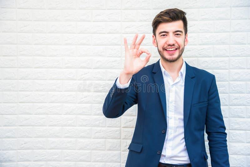 Красивый бизнесмен делая о'кей или alright показывать Дело и стоковое изображение rf