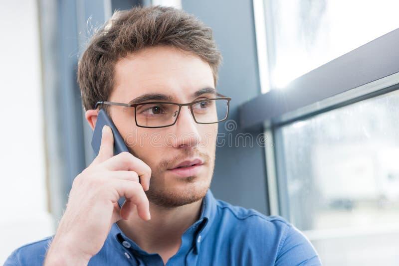 Красивый бизнесмен используя smartphone стоковое изображение rf