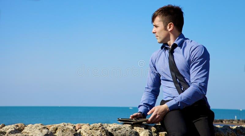 Красивый бизнесмен ослабляя с таблеткой перед океаном стоковая фотография