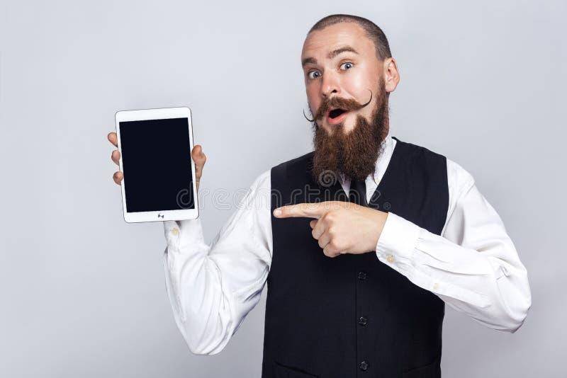 Красивый бизнесмен при усик бороды и handlebar держа цифровую таблетку и смотря камеру и показывая экран с пальцем стоковые изображения