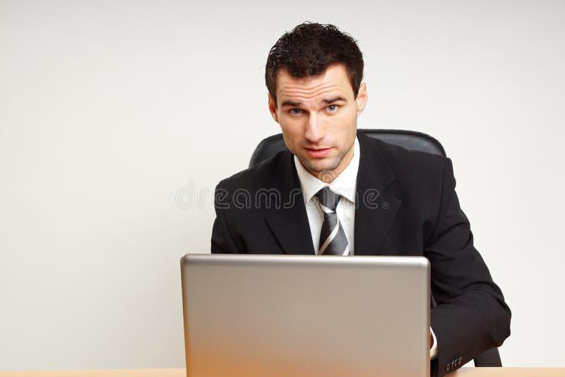 Красивый бизнесмен работает на компьютере стоковое изображение