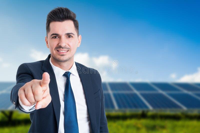 Красивый бизнесмен с панелями солнечных батарей за им стоковые изображения