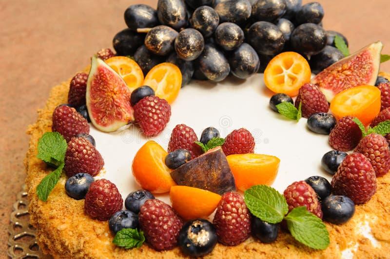 Красивый большой торт меда украшенный с kandurin золота груш плодоовощей и крушины моря, виноградинами, смоквами, кумкватом стоковые изображения rf